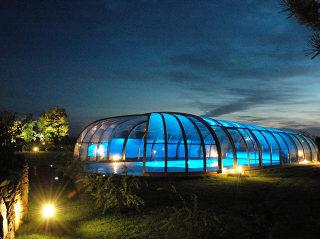 Der Nachtblick auf Premium Poolüberdachung OLYMPIC™ von Alukov