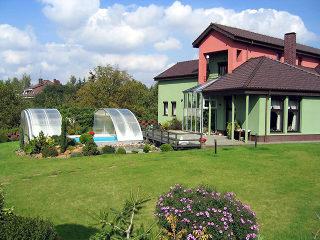 Zu großem Garten passt die RAVENA Poolüberdachung ideal.