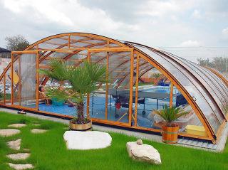 Elegante Ausführung - abgerundete Form der Poolüberdachung UNIVERSE mit Profilen im Holzdekor
