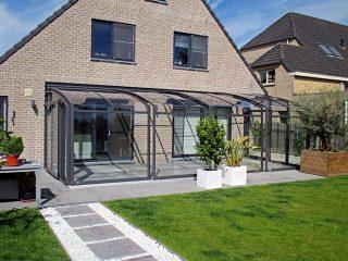 Schiebbare Terrassenüberdachung Corso Premium passt hervorragend zu untypischem Objekt