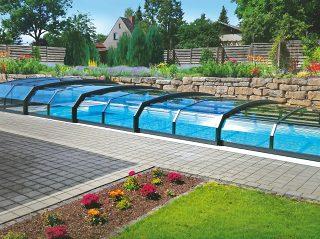 Schwimmbadüberdachung Oceanic flach fügt sich wunderbar in einen blühenden Garten.