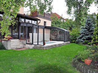 Im Garten wunderschön integrierte Terrassenüberdachung CORSO Premium