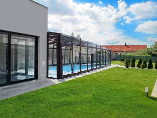 Hohes Poolüberdachungsmodell VISION direkt mit dem Haus verbunden