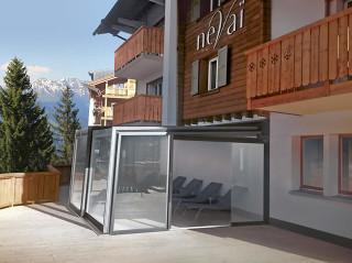 Moderne Überdachung als Bestandteil des traditionellen Berghotels