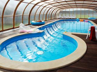 Untypisches Schwimmbad mit der LAGUNA Schwimmbadüberdachung ergänzt