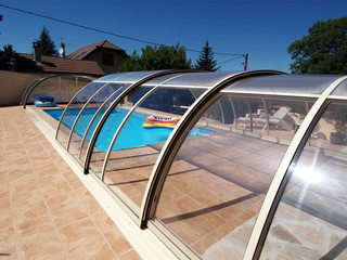Mittelhohe Schwimmbadüberdachung TROPEA mit klarem Polykarbonat