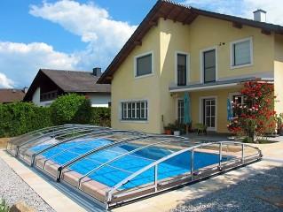 Schwimmbadüberdachung Imperia mit modernem Haus im Hintergrund