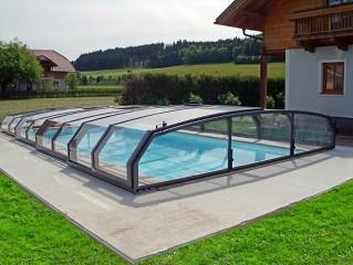 Schwimmbadüberdachung Oceanic flach mit klassischem Haus im Hintergrund