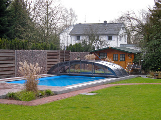 Perfect match of wooden house and wood-like imitation on pool enclosure
