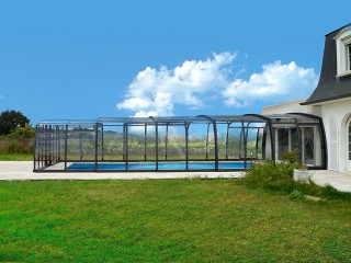 Open retractable pool enclosure with open door by a house