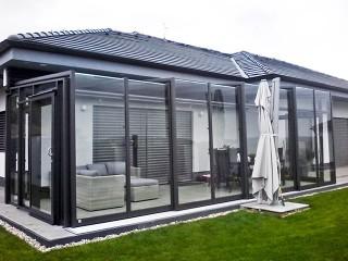 Antracitové provedení terasového zastřešení Corso Glass skvěle ladí s moderním domem