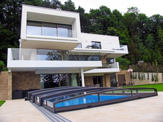 Nízká řada bazénového zastřešení Viva s moderním domem v pozadí