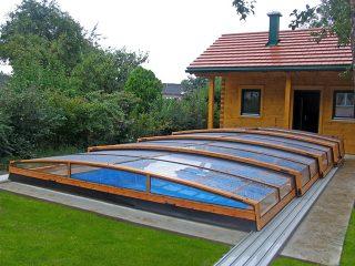 Nízké zastřešení bazénu CORONA™ v barvě imitující dřevo se krásně hodí k dřevostavbám
