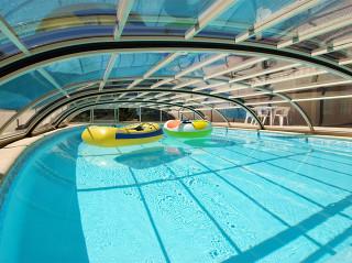 Pohled pod zastřešení bazénu ELEGANT NEO™ v béžové barvě