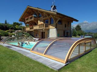 Lidé v bazénu pod zastřešením ELEGANT s hliníkovými profily v barvě imitace dřeva