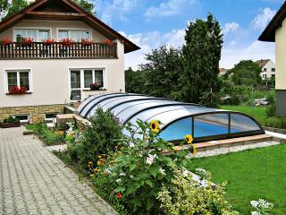 Zastřešení bazénu ELEGANT NEO™ v zahradě rodinného domu