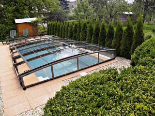 Nízké zastřešení bazénu VIVA™ nenaruší celkový vzhled Vaší zahrady