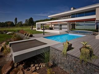 Zastřešení bazénu Viva v bílém provedení perfektně ladí k atypickému domu