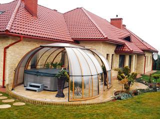 Oválné zastřešení vířivky SPA SUNHOUSE® ladí s oblými doplňky v zahradě