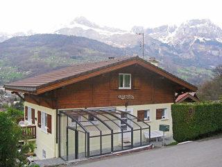 Auf Maß angefertigte Schiebeüberdachung mit schweizerischen Bergen im Hintergrund