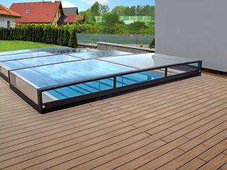 Die neidrigste Schwimmbadüberdachung Terra passt sehr gut zum Holzboden.