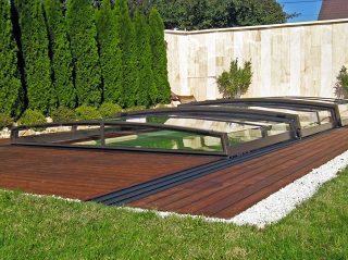 Modell Corona aus der flachen Serie der Schwimmbadüberdachungen hier bestens passend zum Holzboden.