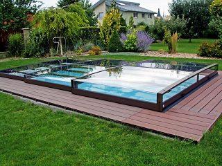 Schwimmbadüberdachung Terra fügt sich wunderbar in blühenden Garten ein.