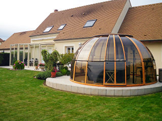 Terrassenüberdachung CORSO Glas hinten - vorne die Spaüberdachung SPA DOME ORLANDO im Holzdekor