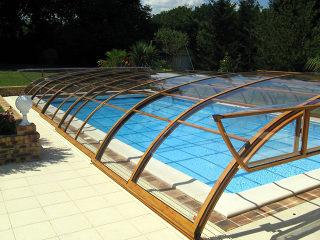 Abri de piscine rétractable Elegant NEO avec la face avant relevée pour éviter les obstacle lors du coulissage