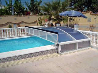 Abri de piscine rétractable IMPERIA NEO clair avec face avant relevée pour permettre de nager dans la longueur de la piscine