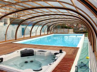 Cadre en imitation bois sur l'abri de piscine LAGUNA par-dessus une piscine et un jacuzzi
