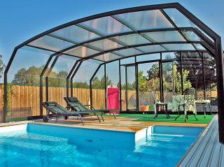 Abri de piscine OCEANIC en cadres foncés recouvrant partiellement un espace salon