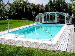 Abri de piscine rétractable OCEANIC - cadres blancs - repliés à l'extrémité de la piscine