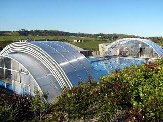 Abri de piscine UNIVERSE NEO replié de manière télescopique loin de la piscine