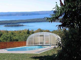 L'abri de piscine LAGUNA entièrement rétracté avec belle vue en arrière-plan
