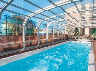 L'abri de piscine télescopique OCEANIC HIGH en blanc avec abri de spa dôme Orlando en arrière-plan