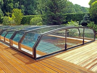 Labri de piscine télescopique OCEANIC LOW a lair élégante grâce à un plancher en bois