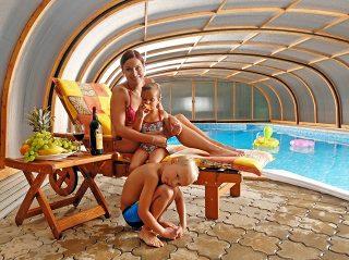 Une famille heureuse profite des avantages de labri de piscine LAGUNA NEO à finition en imitation bois