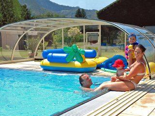 Une famille heureuse profite des jours dété sous labri de piscine TROPEA NEO
