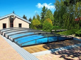 Pool enclosure Corona fits great into garden with modern house in the background
