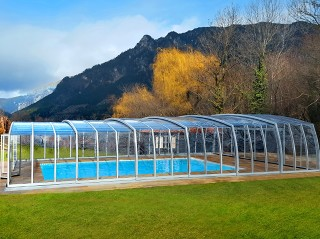 Copertura per piscina Omega in colore argento con le montagne in fondo