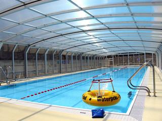 Copertura telescopica per piscina con profili in alluminio e policarbonato impacchettata in fondo della piscina