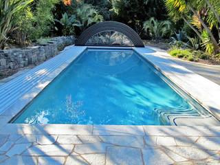 copertura telescopica per piscina modello Universe con la porta frontale a batente