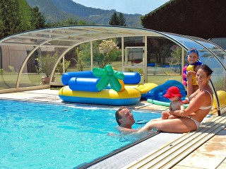 Happy family is enjoing summer days under pool enclosure Tropea NEO