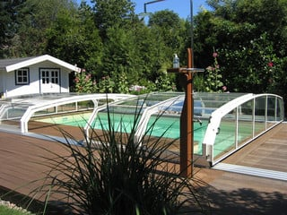 Dark color used on construction of pool cover OCEANIC in a spring meadow