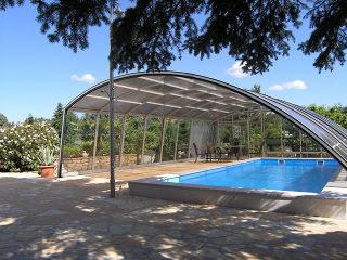 Telescopische Zwembadoverkapping RAVENA beschermt het zwembad van wind, regen en pollutie