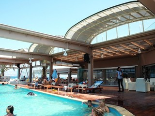 Multiple automated roof enclosures over hotel pool and bar