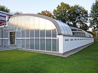 A multi-segment lean-to enclosure used to enclose 30 meters long public pool - opened for better air circulation