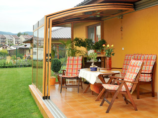 Patio enclosure CORSO Solid - fully opened and equipped with patio furniture