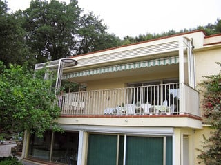 Retractable patio enclosure CORSO Solid used as a balcony enclosure